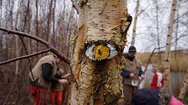a tree with a painted face at the marsh monster event at how hill